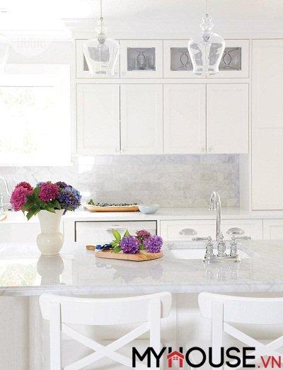 Không gian nhà bếp màu trắng được trang bị quầy bar được thiết kế bằng đá cẩm thạch và đá thạch anh màu trắng cho không gian trở nên sáng bừng lên